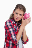 Portrait of a sad woman shaking a piggy bank. Against a white background Royalty Free Stock Photo