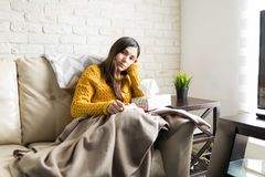 Ill Woman With Tissue Box. Portrait of sad woman sitting on sofa while suffering from cold at home royalty free stock photo