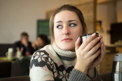 Portrait of sad woman in sweater drinking coffee at cafe Stock Photo
