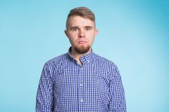 Portrait of sad young man on blue background Stock Photo