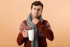 Portrait of a sad young man dressed in sweater. And scarf holding cup with tea isolated over beige background, having sore throat stock photography