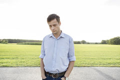 Portrait of sad young man with hands in pockets standing on rural road Stock Image