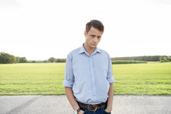 Portrait of sad young man with hands in pockets standing on rural road Royalty Free Stock Photo