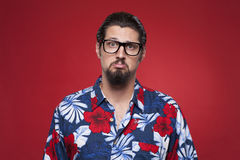 Portrait of a sad young man in Hawaiian shirt against red backgr Stock Photo