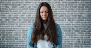 Portrait of sad young woman looking around then at camera on brick background stock footage
