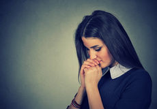 Portrait of sad young woman praying with eyes closed. Closeup portrait of sad young woman praying with eyes closed Royalty Free Stock Photos