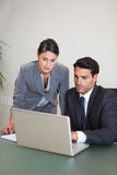 Portrait of sales persons working with a notebook Royalty Free Stock Photos