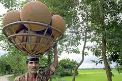Portrait of salesman carrying basket pottery bowls. Bangladesh, in the countryside just outside Tangail lugging a man, street trader, with terracota pots, bowls Stock Photos