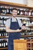 Portrait Of Salesman Holding Wine Bottle royalty free stock photography