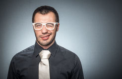 Portrait of salesman with shirt and necktie. Stylished positive businessman winking and wearing eyeglasses against dark isolated gray background with copyspace Stock Images