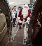 Portrait Of Santa Boarding Private Jet. With stewardess and captin standing in background Stock Photo