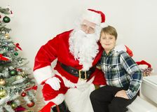 Portrait of Santa Claus and a boy. In the center of this horizontal image is a Santa Claus is hugging a boy near christmas tree. Boy is wearing a dark and light Stock Images