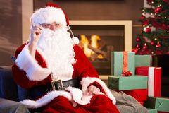 Portrait of Santa Claus by fireplace. Raising pointing finger, looking at camera Royalty Free Stock Photography