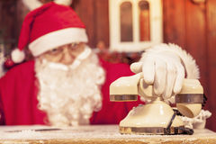 Portrait of santa claus gets a call at his home. Compiles the wishlist for christmas royalty free stock photo