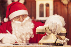 Portrait of santa claus gets a call at his home. Compiles the wishlist for christmas royalty free stock image