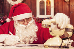 Portrait of santa claus gets a call at his home. Compiles the wishlist for christmas royalty free stock images