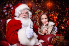 Portrait with santa claus. A happy young girl is near Santa Claus at home. Merry Christmas and Happy New Year stock photo