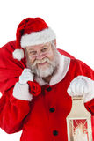 Portrait of santa claus holding christmas bag and lantern Stock Images