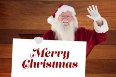 Portrait of santa claus holding christmas greeting. Against wooden background Stock Images