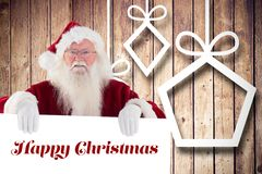 Portrait of santa claus holding christmas greeting. Against wooden background Royalty Free Stock Photo