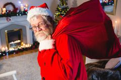 Portrait of santa claus holding gift sack at home Royalty Free Stock Images