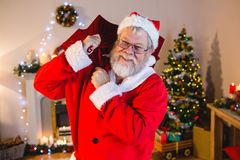 Portrait of santa claus holding gift sack at home Royalty Free Stock Photos