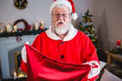 Santa claus holding gift sack at home Stock Photography
