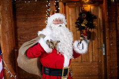 Portrait of Santa Claus holding his bag and ringing a bell it`s Royalty Free Stock Photo