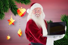Portrait of santa claus holding a laptop Royalty Free Stock Photo