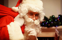 Portrait of Santa Claus with huge red sack keeping forefinger by his mouth and looking at camera. Stock Photos