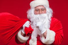 Portrait of Santa Claus with huge red sack keeping forefinger by his mouth and looking at camera Stock Photos