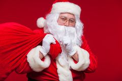 Portrait of Santa Claus with huge red sack keeping forefinger by his mouth and looking at camera Royalty Free Stock Photo