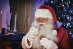 Portrait of Santa Claus with Milk and Cookie. Portrait of Man in Santa Claus Costume - with Glass of Milk and Cookie, in a Luxurious White Beard, Santa`s Hat and Stock Photography