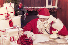 Portrait of santa claus on the phone at his home compiles the wi Stock Photo