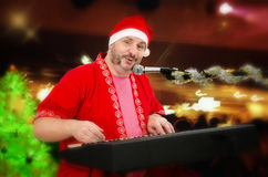 Portrait of Santa Claus playing electric piano. Photo of perky mature man in Santa Claus costume playing electric piano and singing Stock Photo