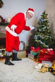 Santa claus showing christmas tree at home royalty free stock photo