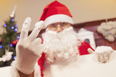 Portrait of santa claus showing two fingers up. At his home Royalty Free Stock Images