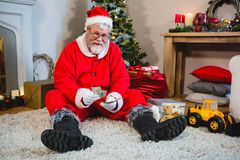 Santa claus sitting on the floor and counting cash at home stock photo