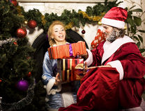 Portrait of Santa Claus with Snow Maiden at Cristmas tree holdin. G gifts at fire place, lifestyle holiday people close up Stock Image