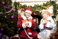 Portrait of Santa Claus with Snow Maiden at Cristmas tree holding gifts. Close up Stock Photo