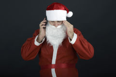 Portrait of Santa talking on mobile looking at camera, isolated Royalty Free Stock Photo