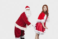 Portrait of Santa touching Mrs. Santa inappropriately against gray background Royalty Free Stock Image