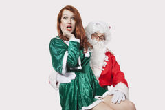 Portrait of Santa touching woman inappropriately against gray background Royalty Free Stock Image