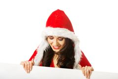Portrait of santa woman holding white banner. Portrait of santa woman holding white empty banner, looking down on it Royalty Free Stock Image