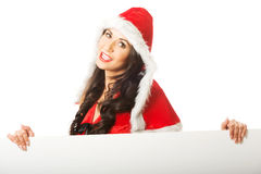 Portrait of santa woman holding white banner, looking at the camera Stock Photo