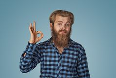 Funny looking guy showing OK sign with fear, uncertainty on his face stock images