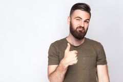 Portrait of satisfied bearded man with thumbs up and dark green t shirt against light gray background. Studio shot Stock Images