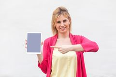 Portrait of satisfied beautiful young woman in pink blouse standing and holding tablet empty screen and pointing finger to device