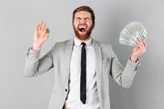 Portrait of a satisfied businessman showing bitcoin Stock Photography