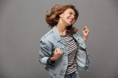Portrait of a satisfied cheerful teenage girl. Dressed in denim jacket celebrating success while dancing  over gray background Royalty Free Stock Image